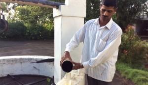 A farm worker measures rainfall in K. K. Naren's coffee farm. (Photo by K. K. Naren)