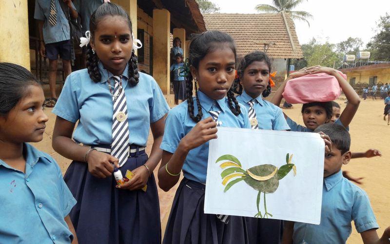 Children demonstrating their art made using leaves.