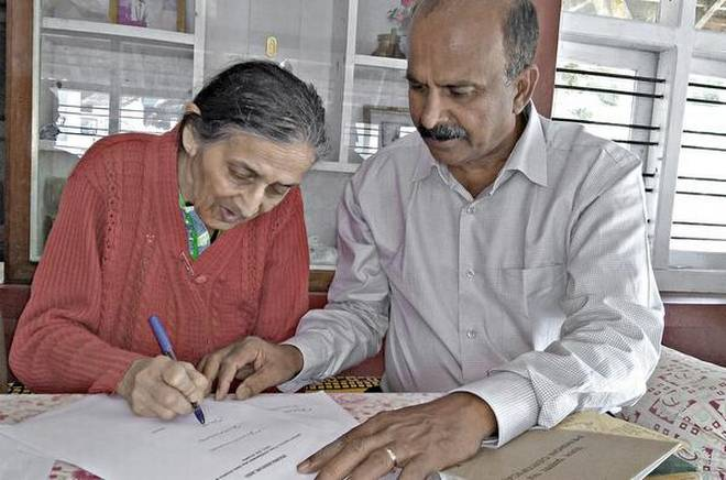 Ex-Sergeant Subramani assisting Kaveriamma in preparing the documents for her fight for pension